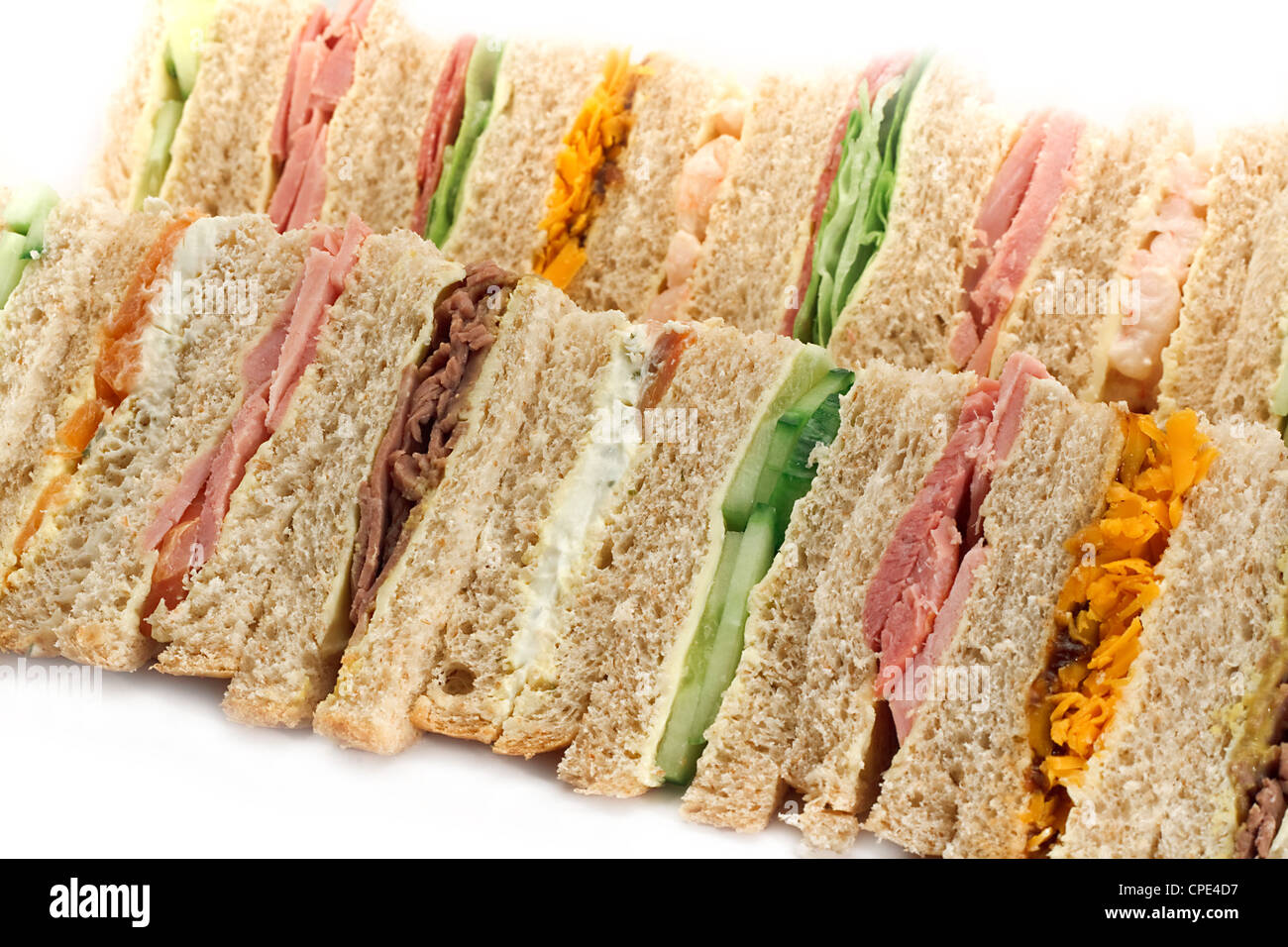 Rows of sandwiches made with sliced bread and cut into triangles - Stock Image