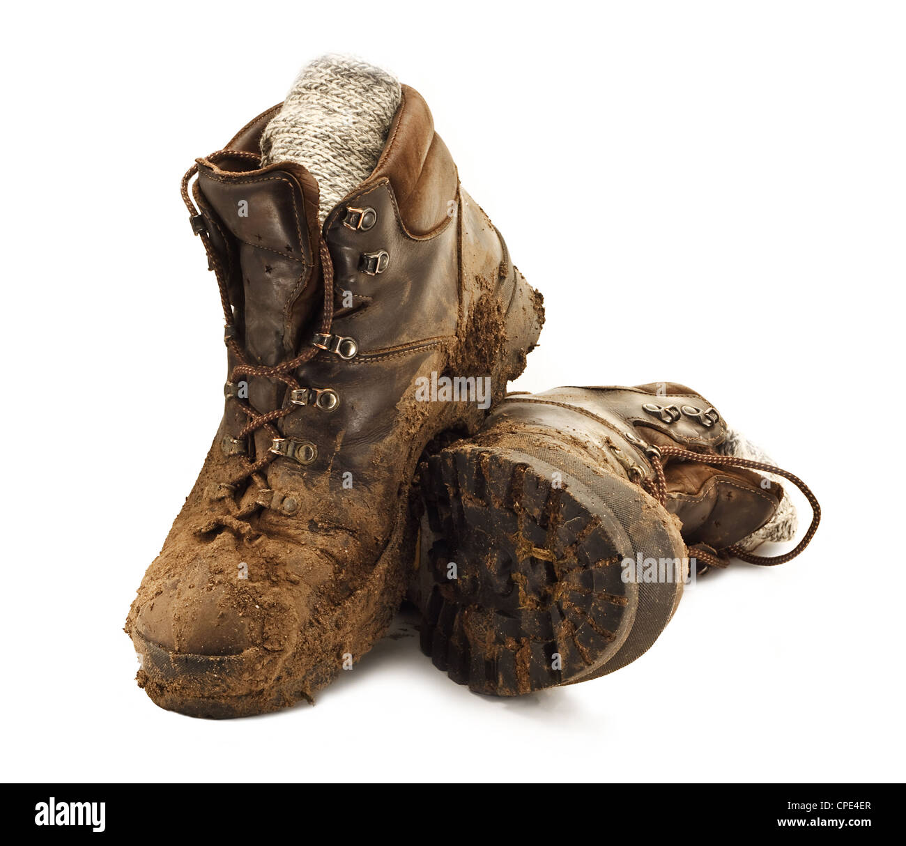 Pair of dirty brown walking boots caked in mud isolated on a white backgound - Stock Image