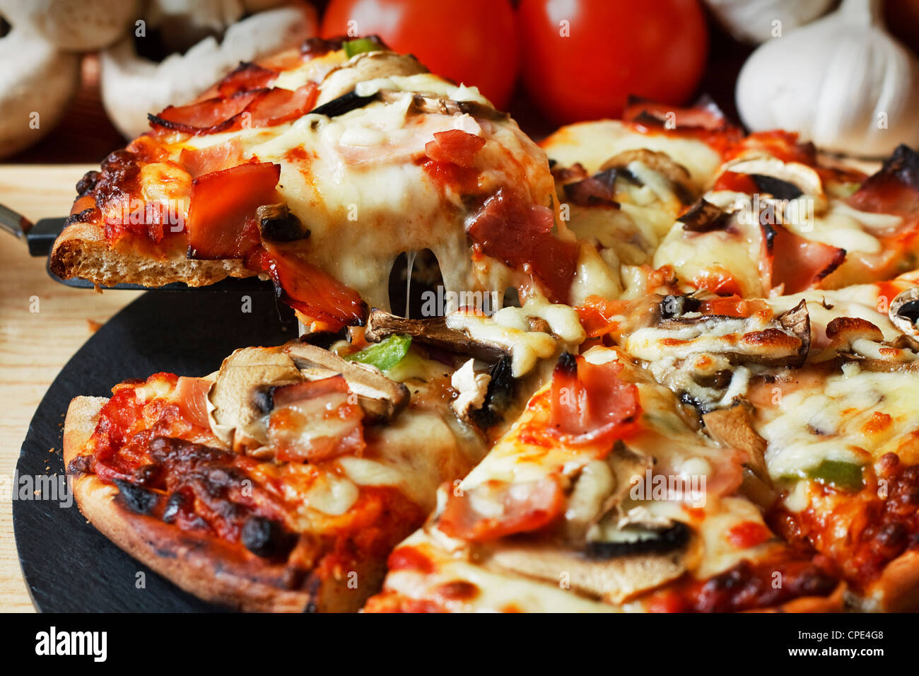 serving slice of ham and mushroom pizza with close up on stringy melted mozzarella cheese - Stock Image