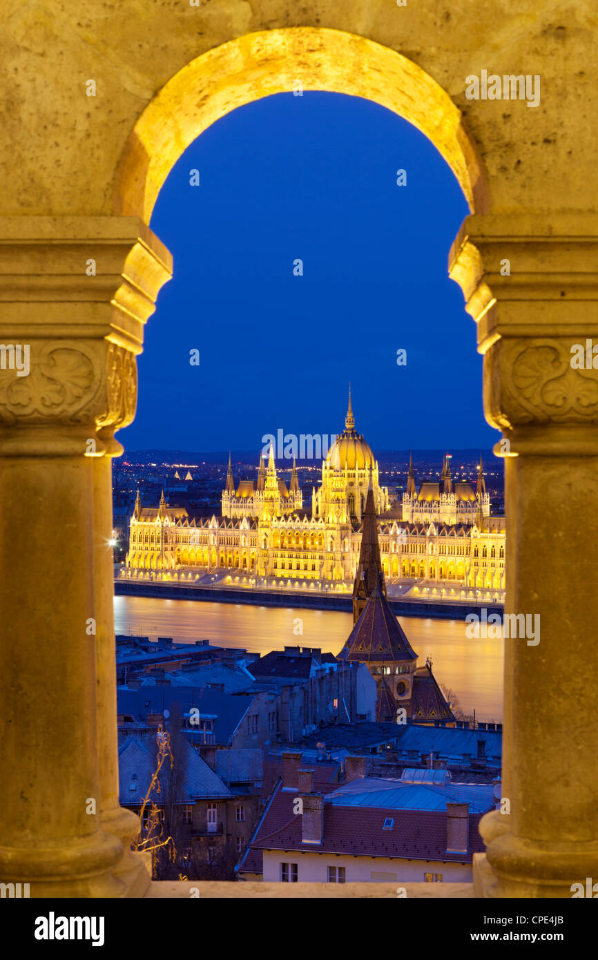 Parliament (Orszaghaz) through arches of Fishermen's Bastion (Halaszbastya) at dusk, Budapest, Hungary, Europe - Stock Image