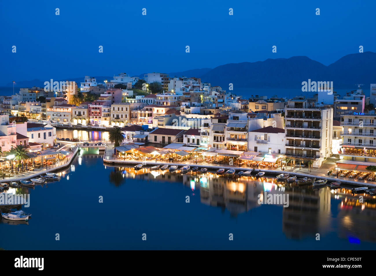 View over harbour and restaurants at dusk, Ayios Nikolaos, Lasithi region, Crete, Greek Islands, Greece, Europe - Stock Image