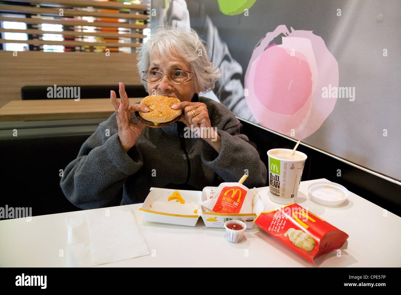 An elderly white haired lady enjoying eating a McDonalds burger, UK - Stock Image