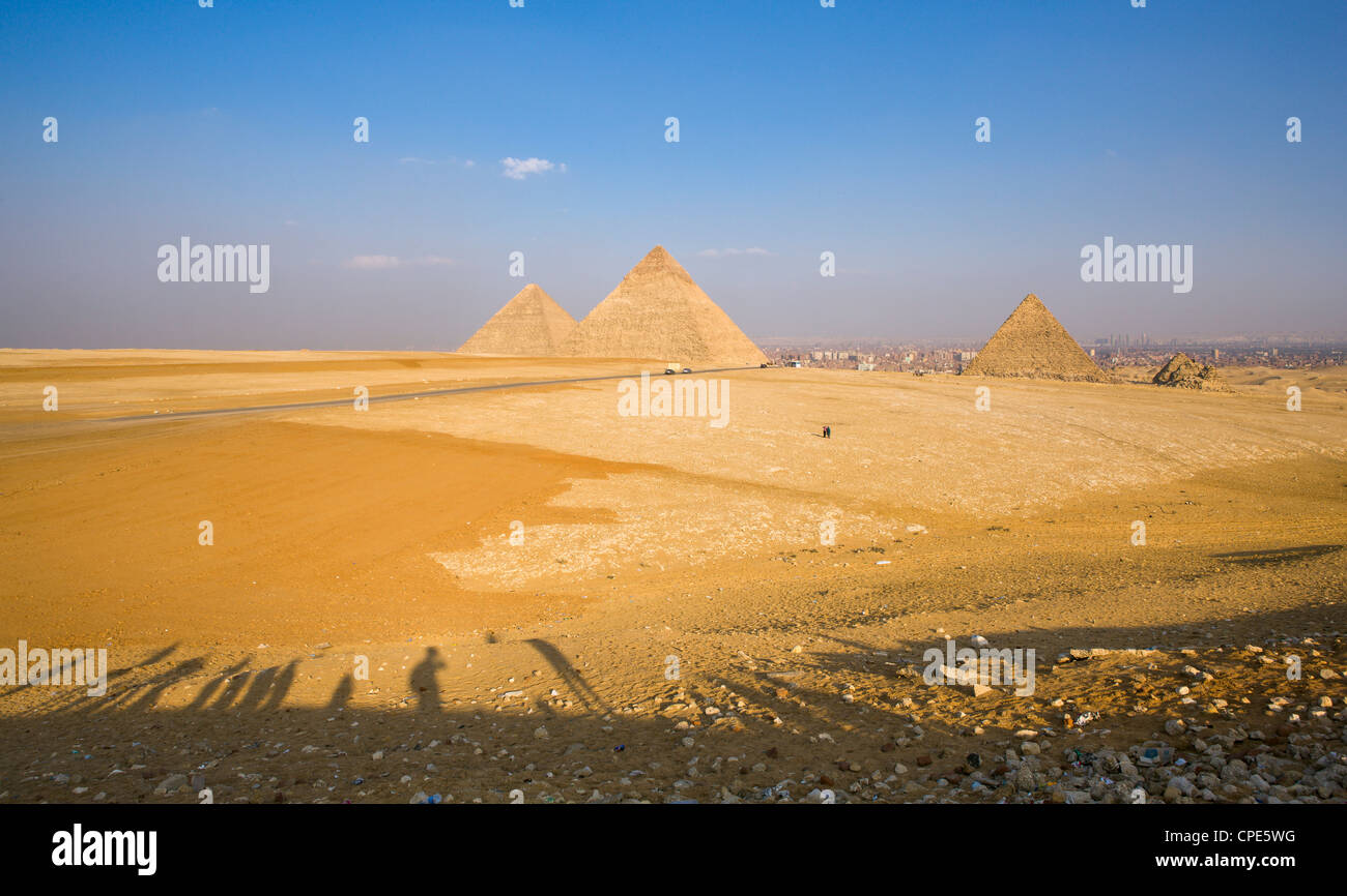 Late shadows of tourists at the viewpoint overlooking the Pyramids of Giza, with Cairo in the background, Egypt, - Stock Image