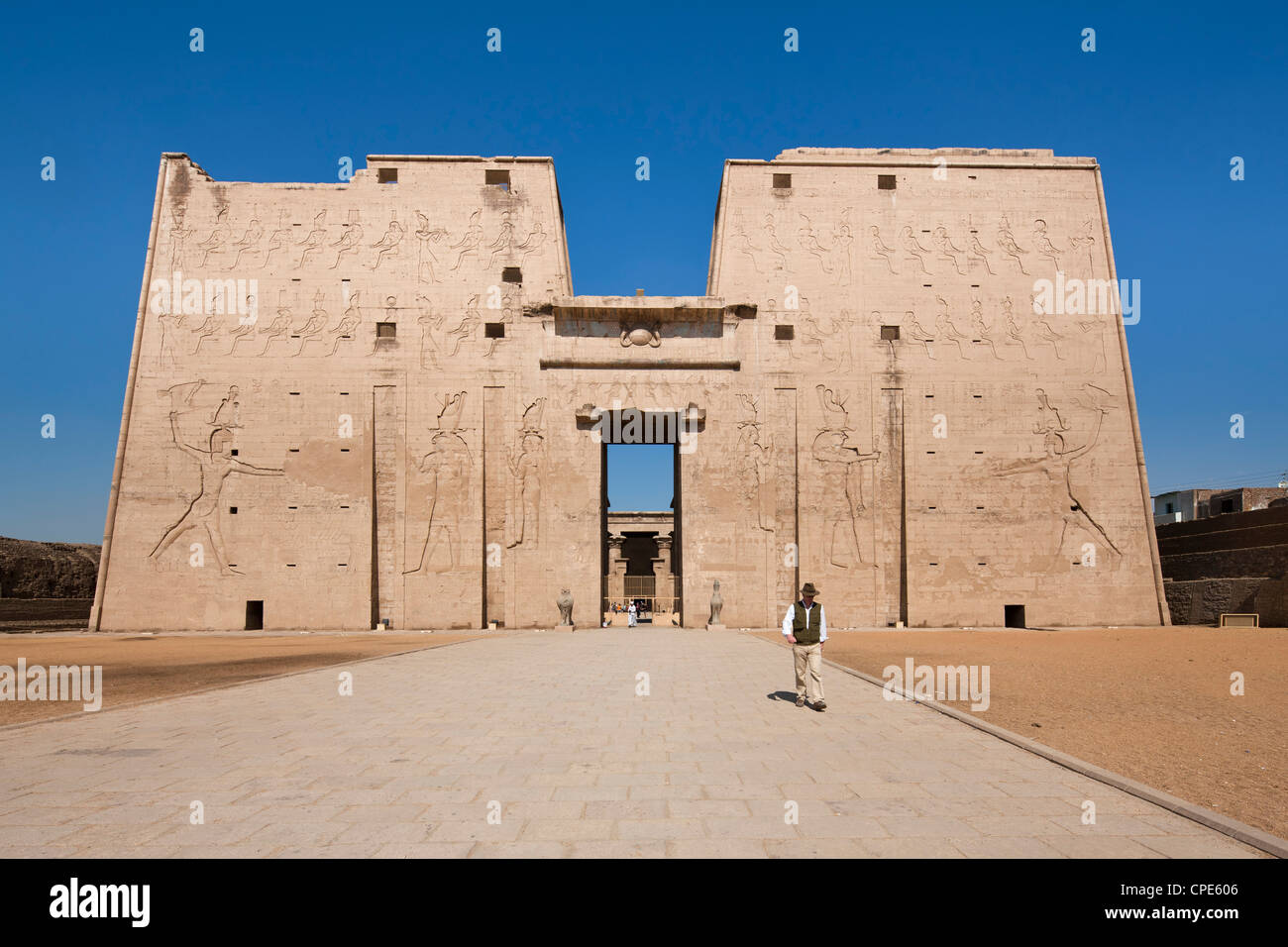 Man standing by the entrance pylon of the Temple of Horus, Edfu, Egypt, North Africa, Africa Stock Photo