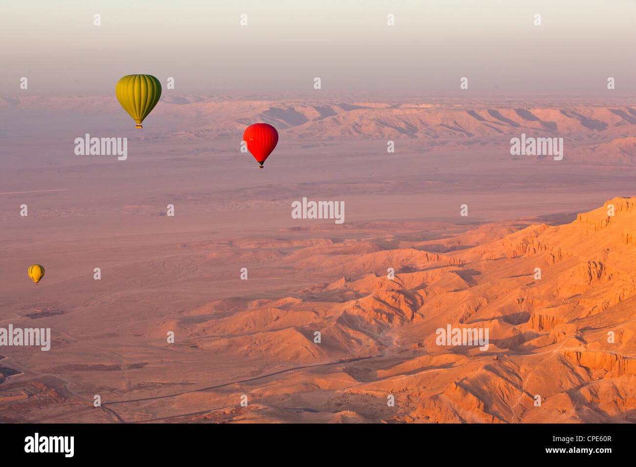 Hot air balloons suspended over the Theban hills of Luxor and the Valley of the Queens at sunrise, Thebes, Egypt, - Stock Image