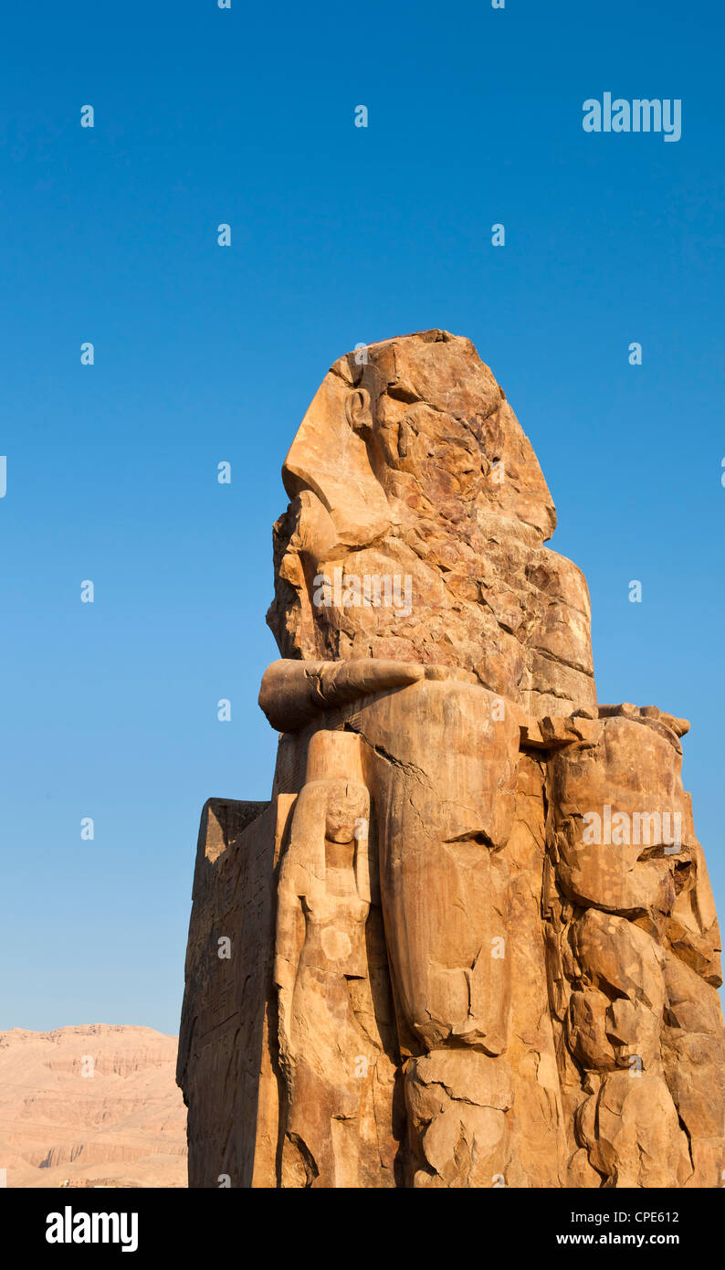 One of the Colossi of Memnon with the Theban hills behind, Thebes, UNESCO World Heritage Site, Egypt, North Africa, - Stock Image