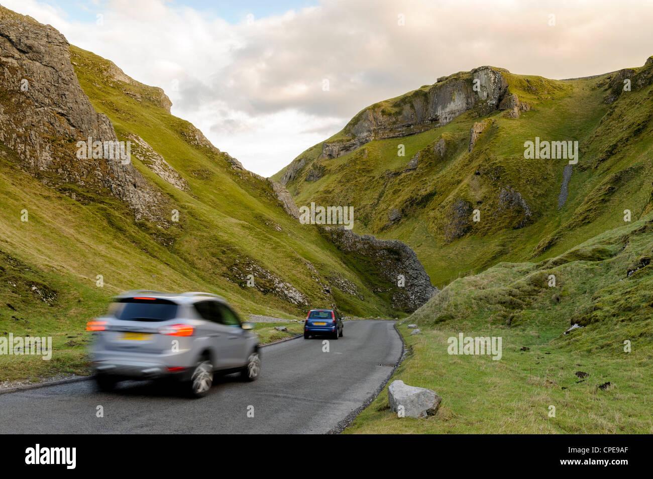 Cars travelling down Winnats Pass, Castleton, Peak District National Park, Derbyshire, England, United Kingdom, - Stock Image