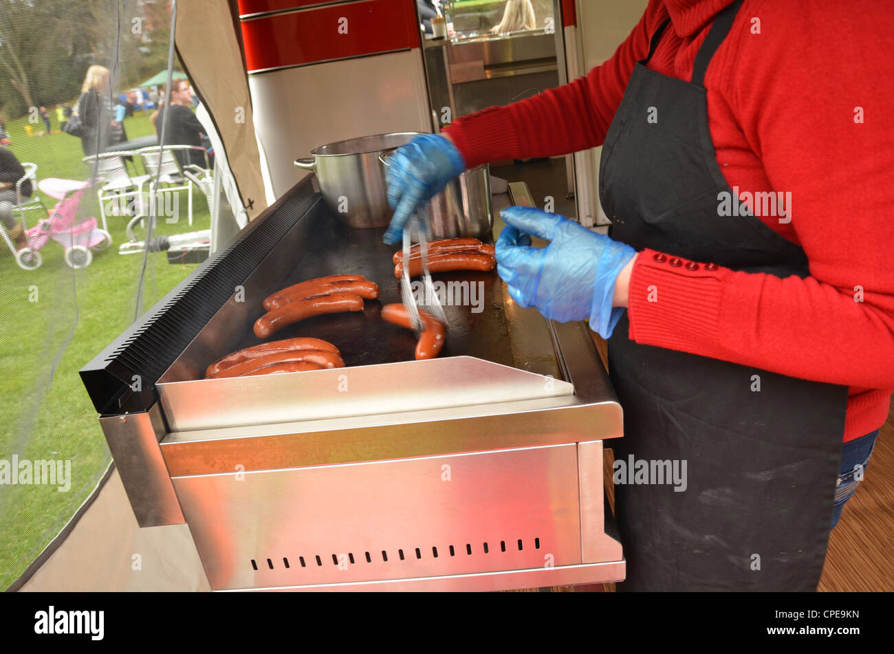 Woman cooking hot dog sausages on griddle at fete - Stock Image