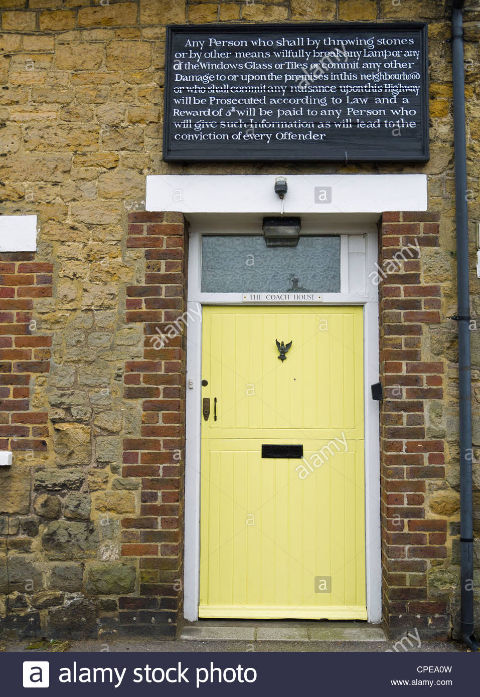 Old Coach House Public Notice to Law Breakers Barton Lane Petworth England Sussex Yellow Door. - Stock Image