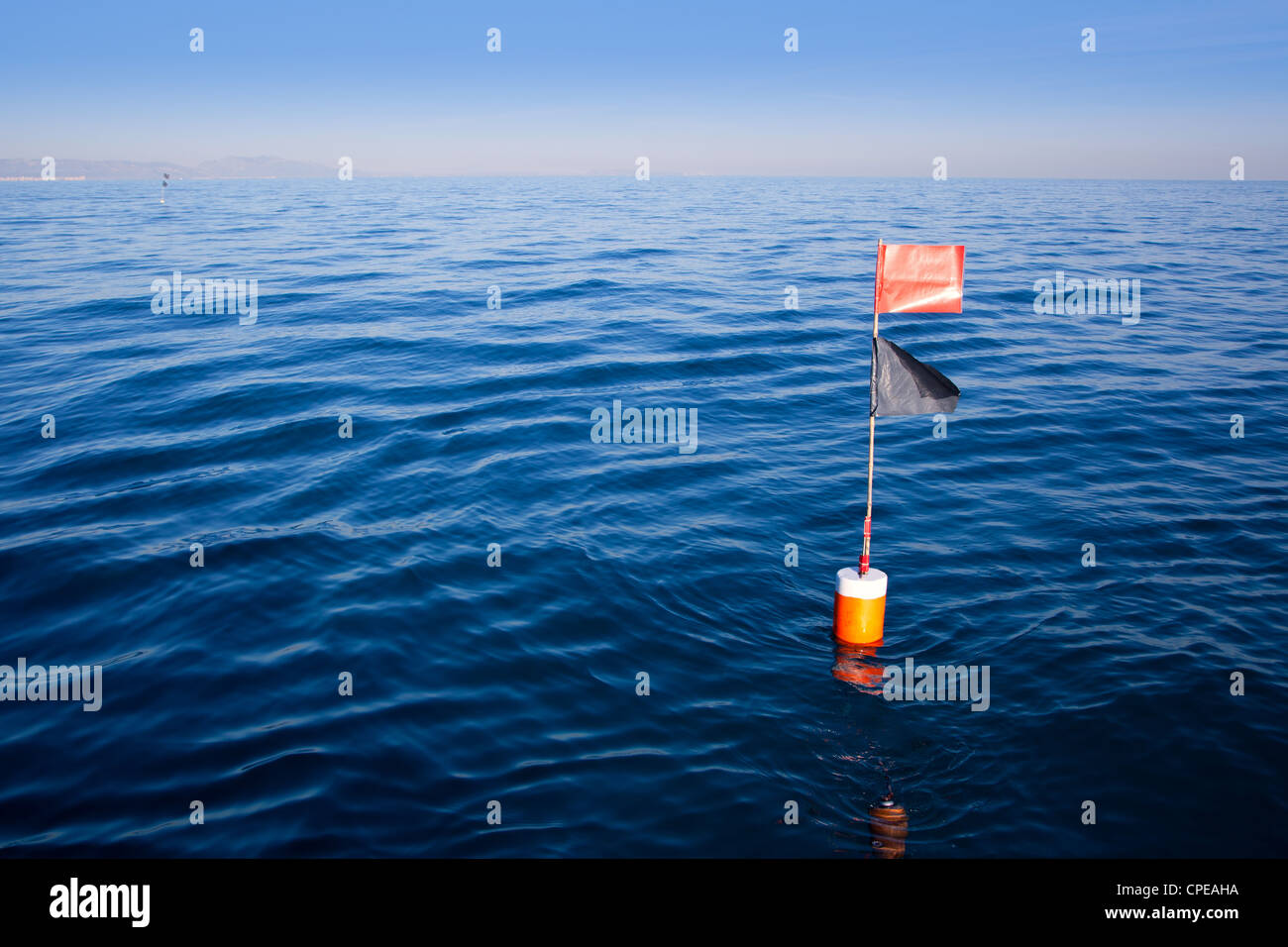 Longliner and trammel net buoy with flag pole in blue sea - Stock Image