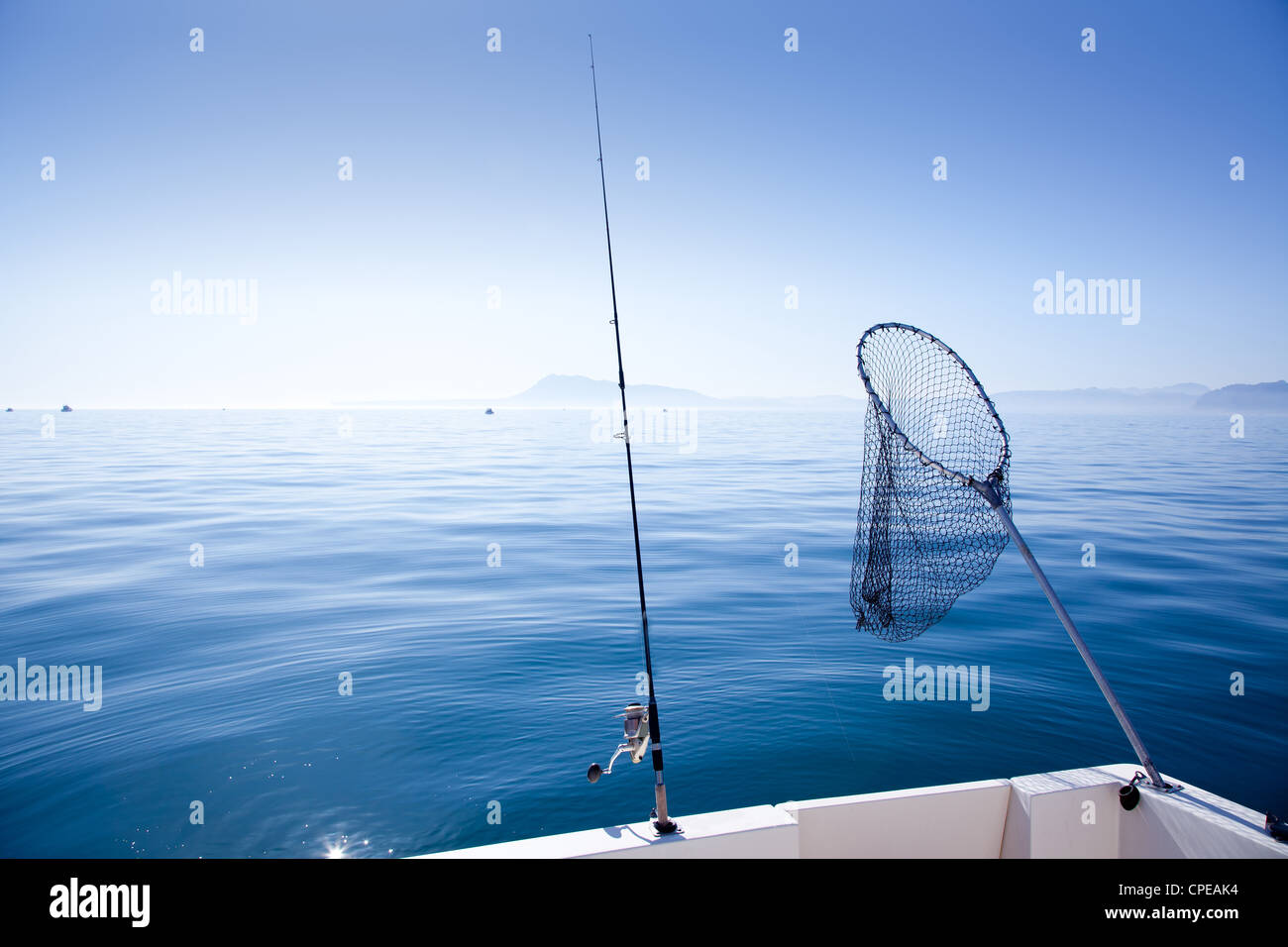 boat fishing rod and landing net in mediterranean blue sea - Stock Image