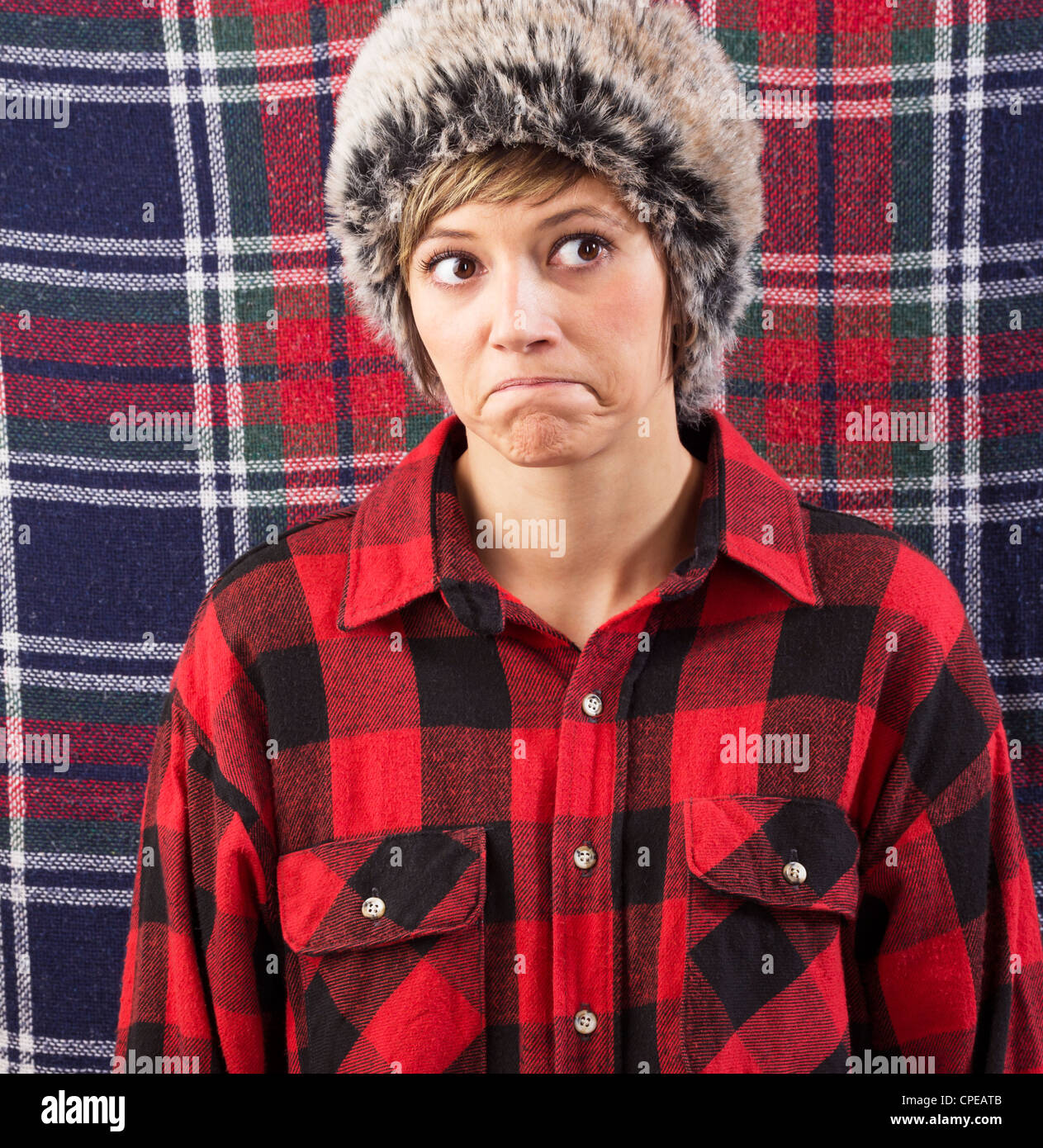 Skeptical pouting young woman wearing a checkered lumberjack shirt and fur hat. Funny studio shot against a patterned - Stock Image