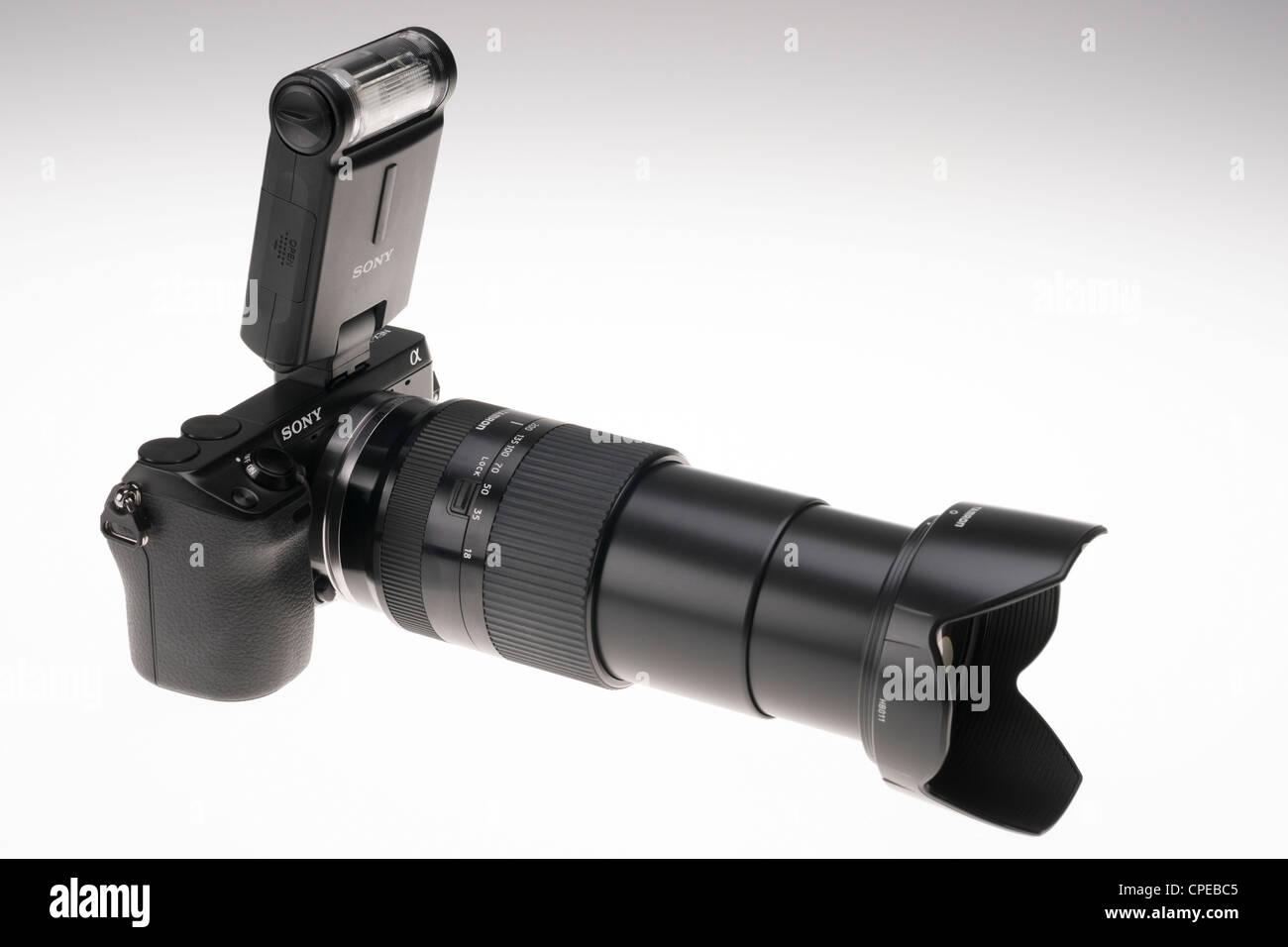 Sony NEX-7 digital mirrorless system camera with 18-200mm Tamron lens and Sony flashgun. - Stock Image