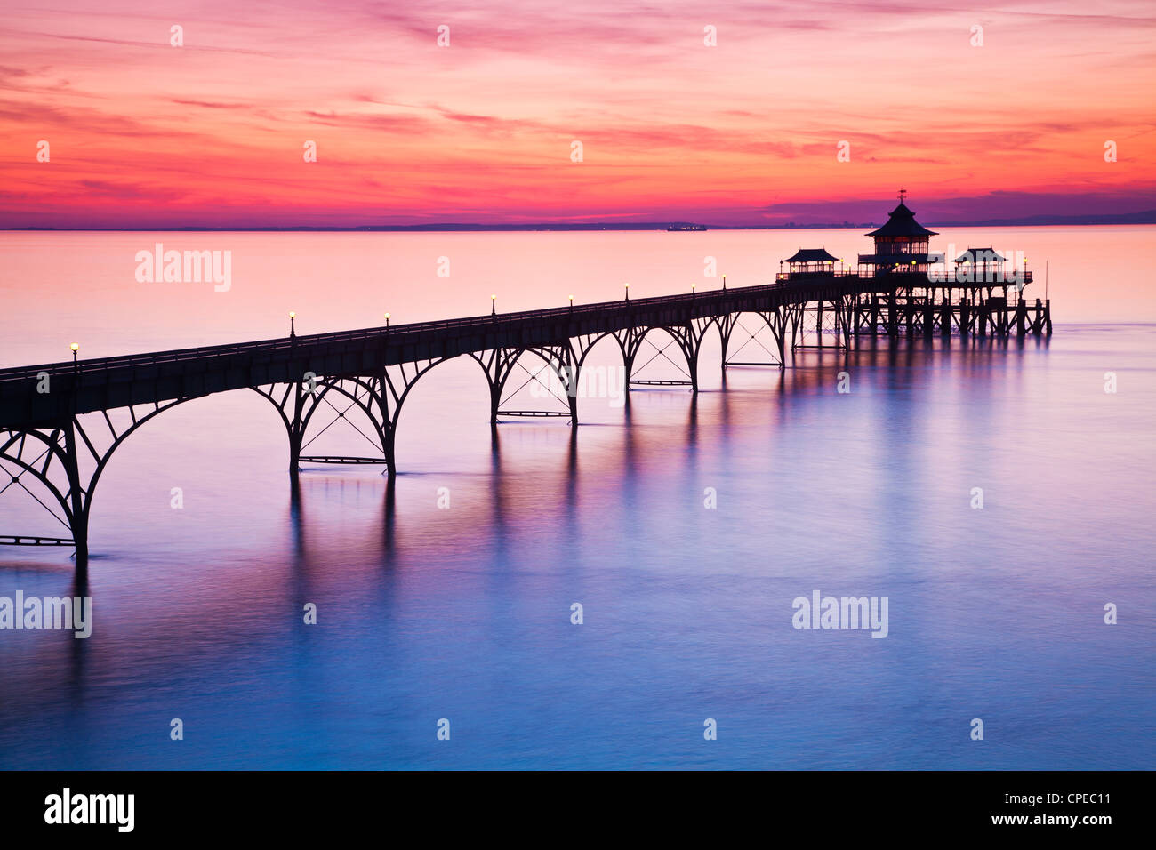The sun sets over the Bristol Channel behind the Pier at Clevedon, Somerset, England, UK Stock Photo