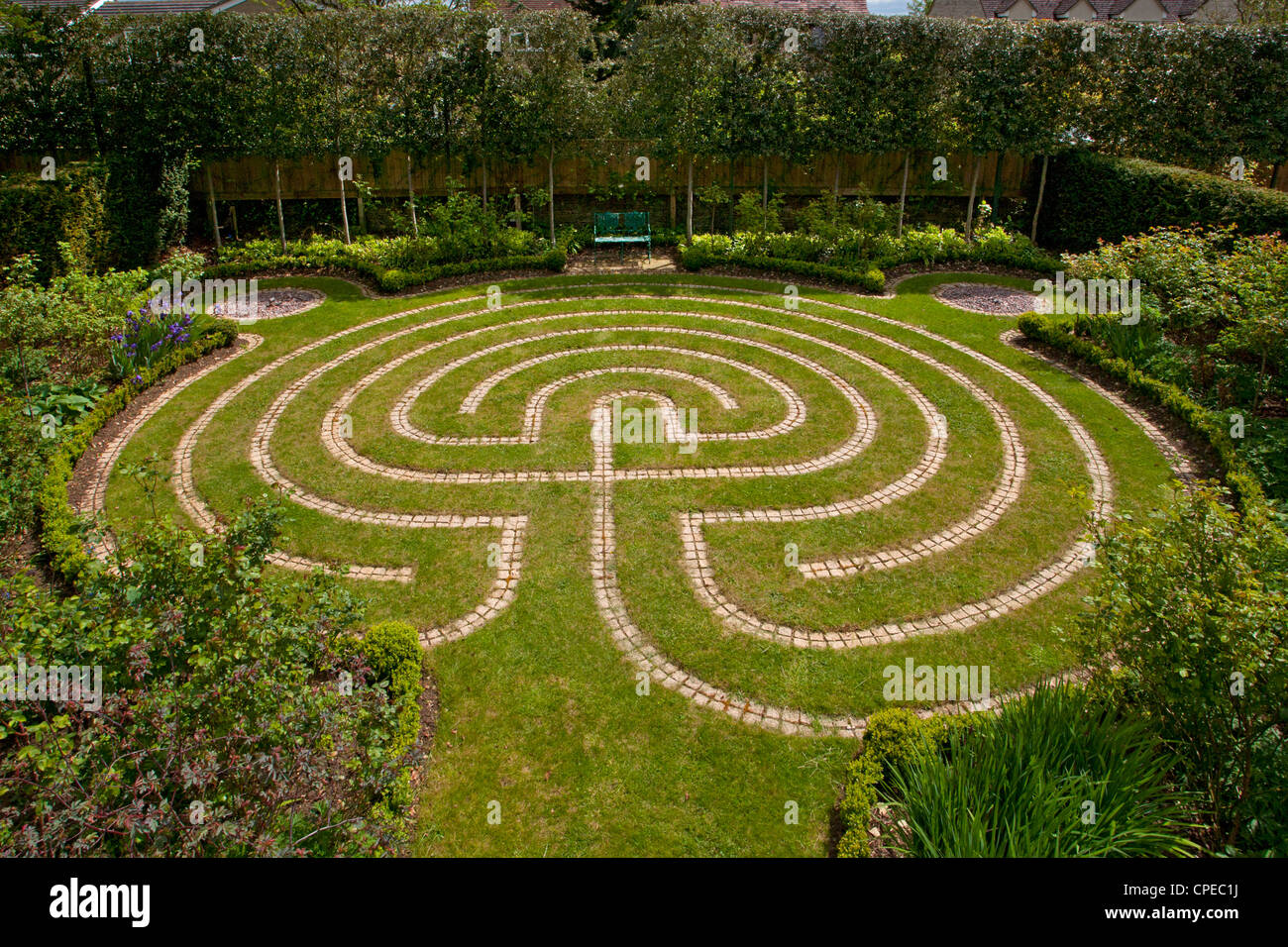 Stone path maze in turf grass lawn at private garden, England - Stock Image