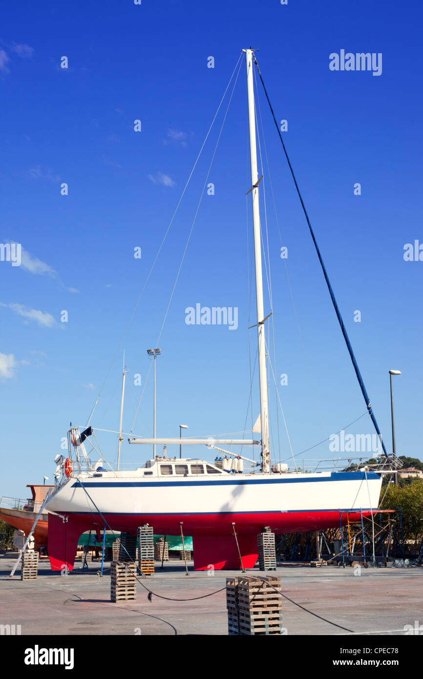 beached sailboat for the yearly hull paint process - Stock Image