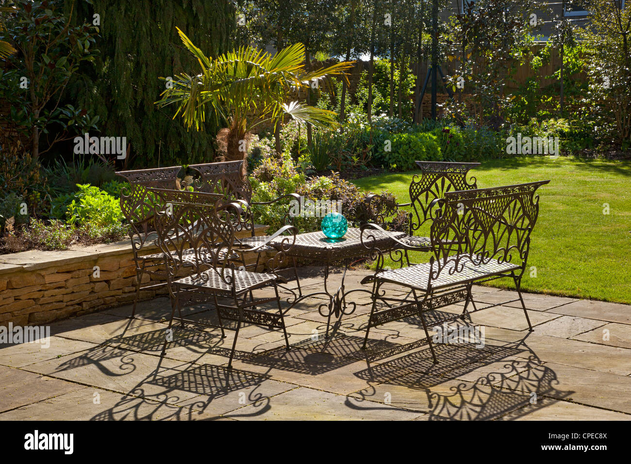 French style metal table and chairs furniture on stone patio in summer garden - Stock Image