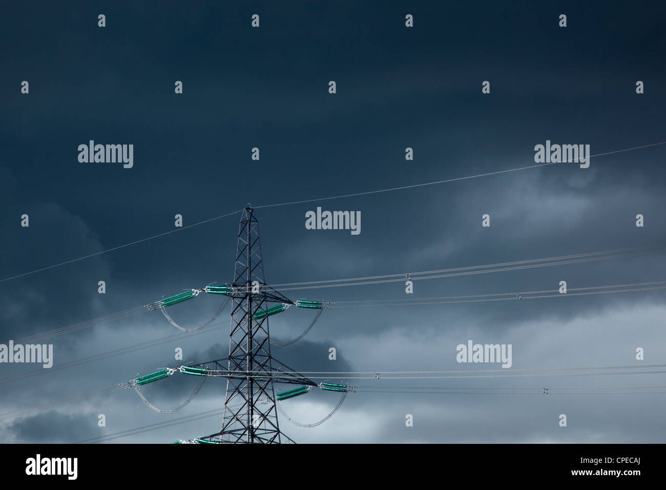 Electricity Pylon and power cables against dark stormy sky, England - Stock Image