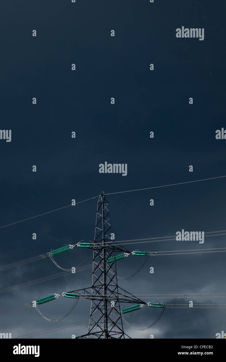 Electricity Pylon and power cables against dark stormy sky,England - Stock Image