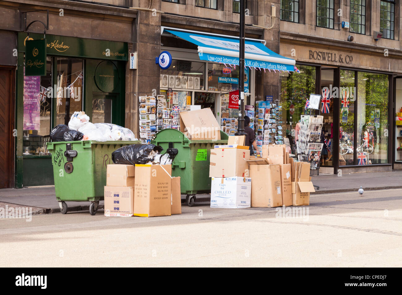 Two skips and several cartons of rubbish or garbage waiting at the kerb for collection, in Broad Street, Oxford, - Stock Image