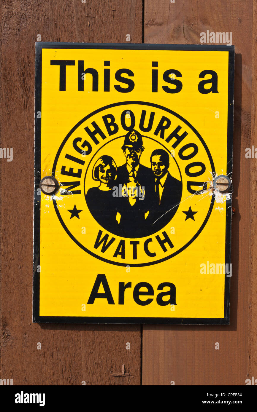 A yellow Neighbourhood Watch street sign on a brown fence - Stock Image