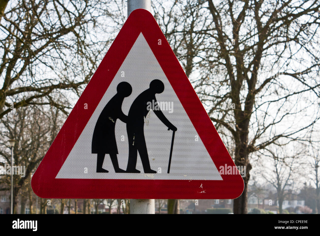 A red triangular road sign warning of frail pedestrians likely to cross road ahead. - Stock Image