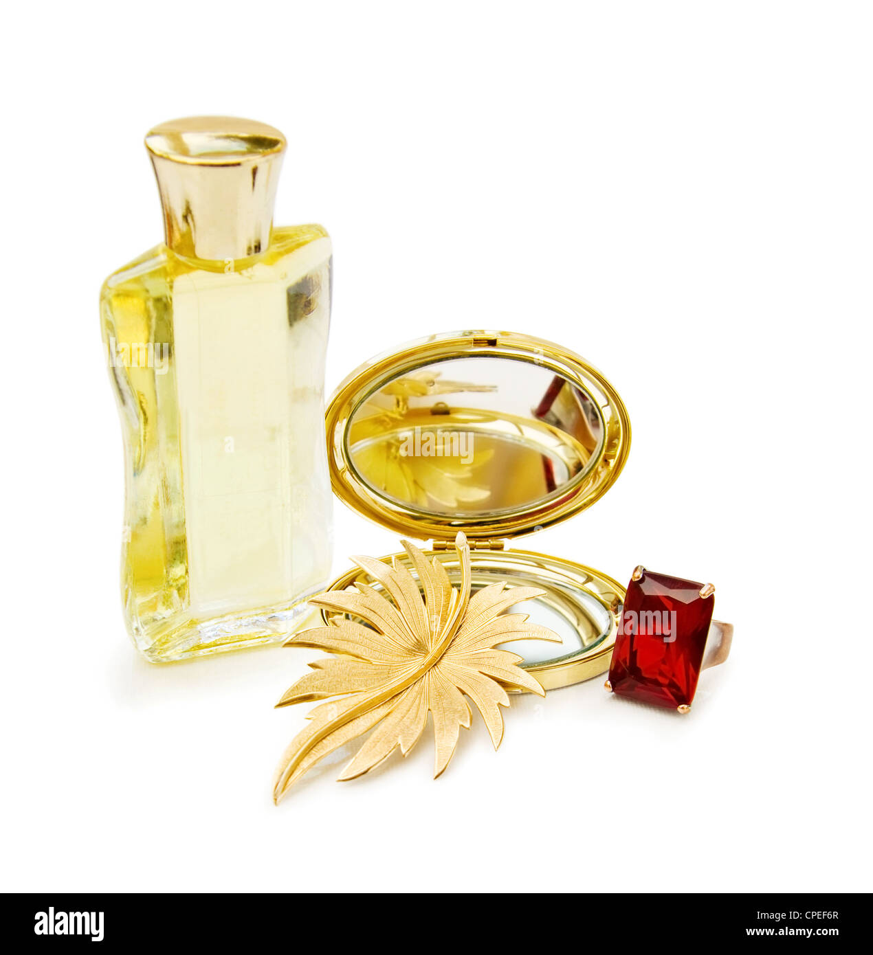 Luxury gift for the celebration of a special day with bottle of perfume, golden mirror and red ruby ring. White - Stock Image