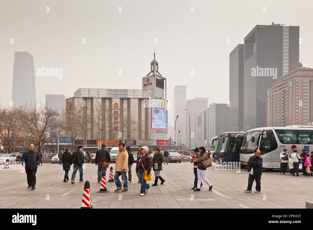 A group of tourists at the Silk Market of Beijing have just left their tour coach. - Stock Image