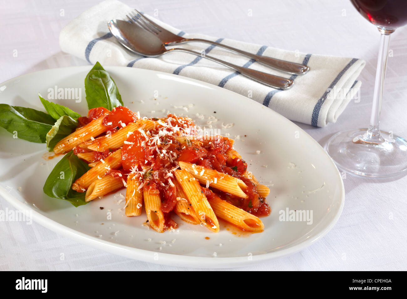 Pasta decorated with basil leaves. White plate on white table cloth, spoon and fork on a napkin. A glass of red - Stock Image