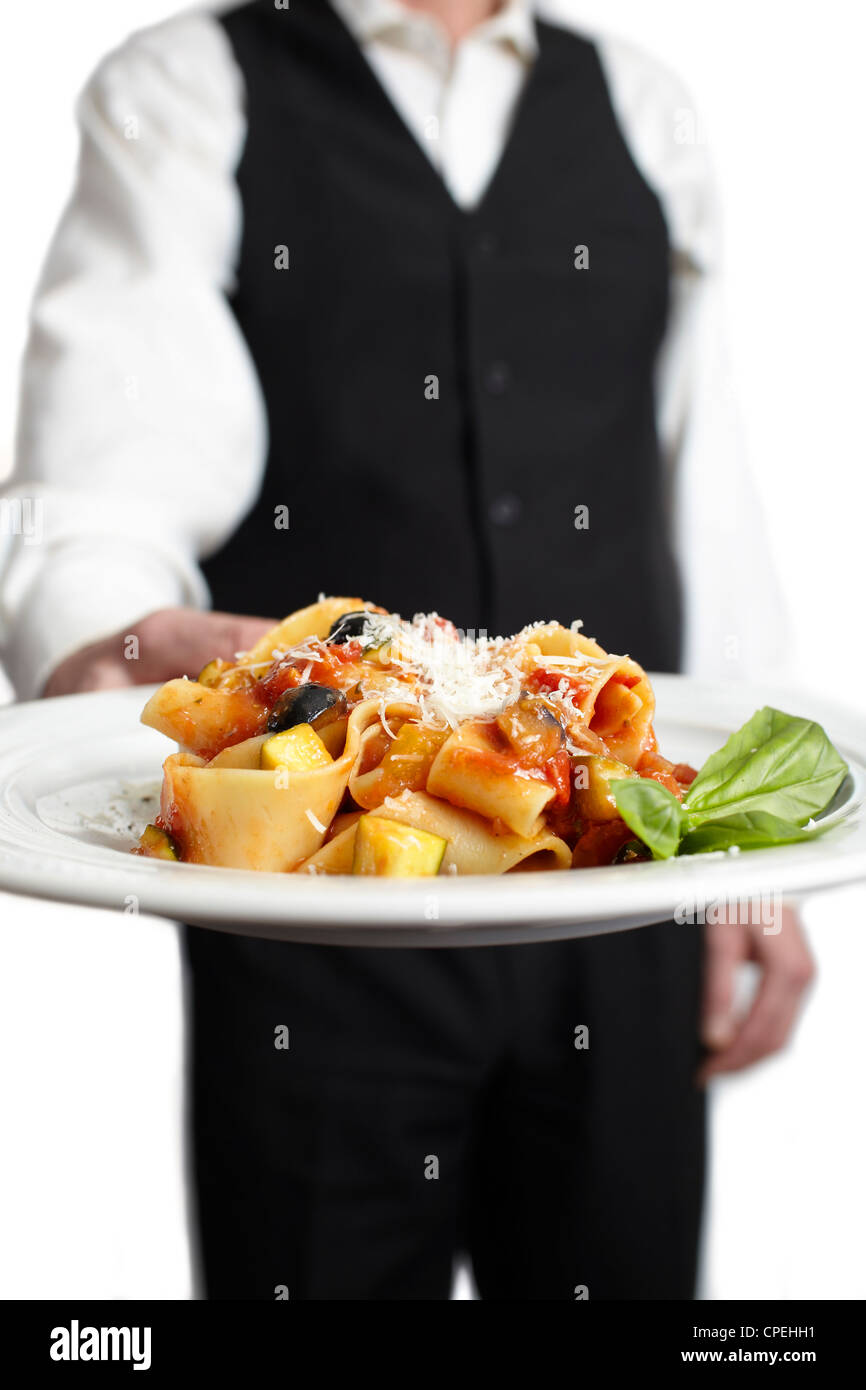 A servant is holding a plate with pasta, tomato sauce, parmesan cheese and basil.€ Focus on plate. Close-up. Stock Photo