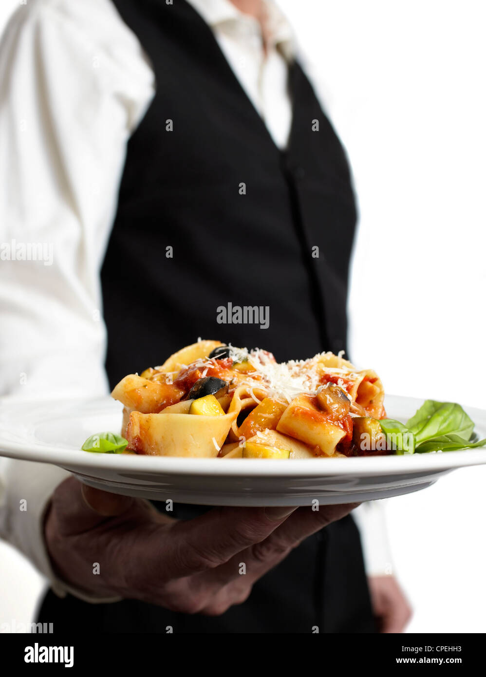A waiter is holding a plate with pasta, tomato sauce, parmesan and basil.€ Focus on plate. Close-up. - Stock Image