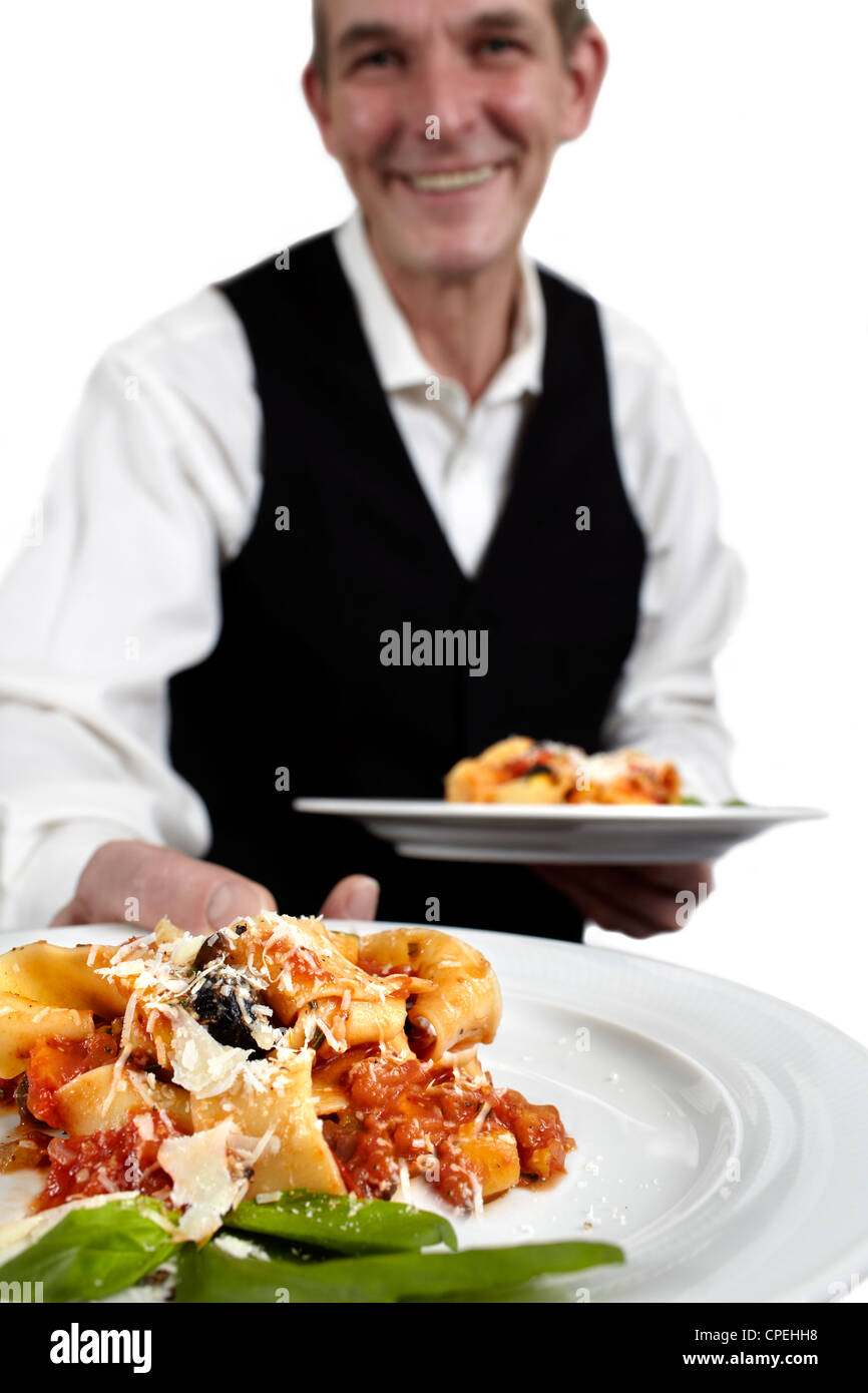 A servant is holding a plate with pasta, tomato sauce, parmesan cheese and basil.€ Focus on plate. Close-up. - Stock Image