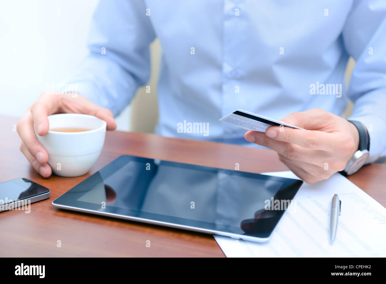 Businessman using a credit card and digital tablet for buying on-line. - Stock Image