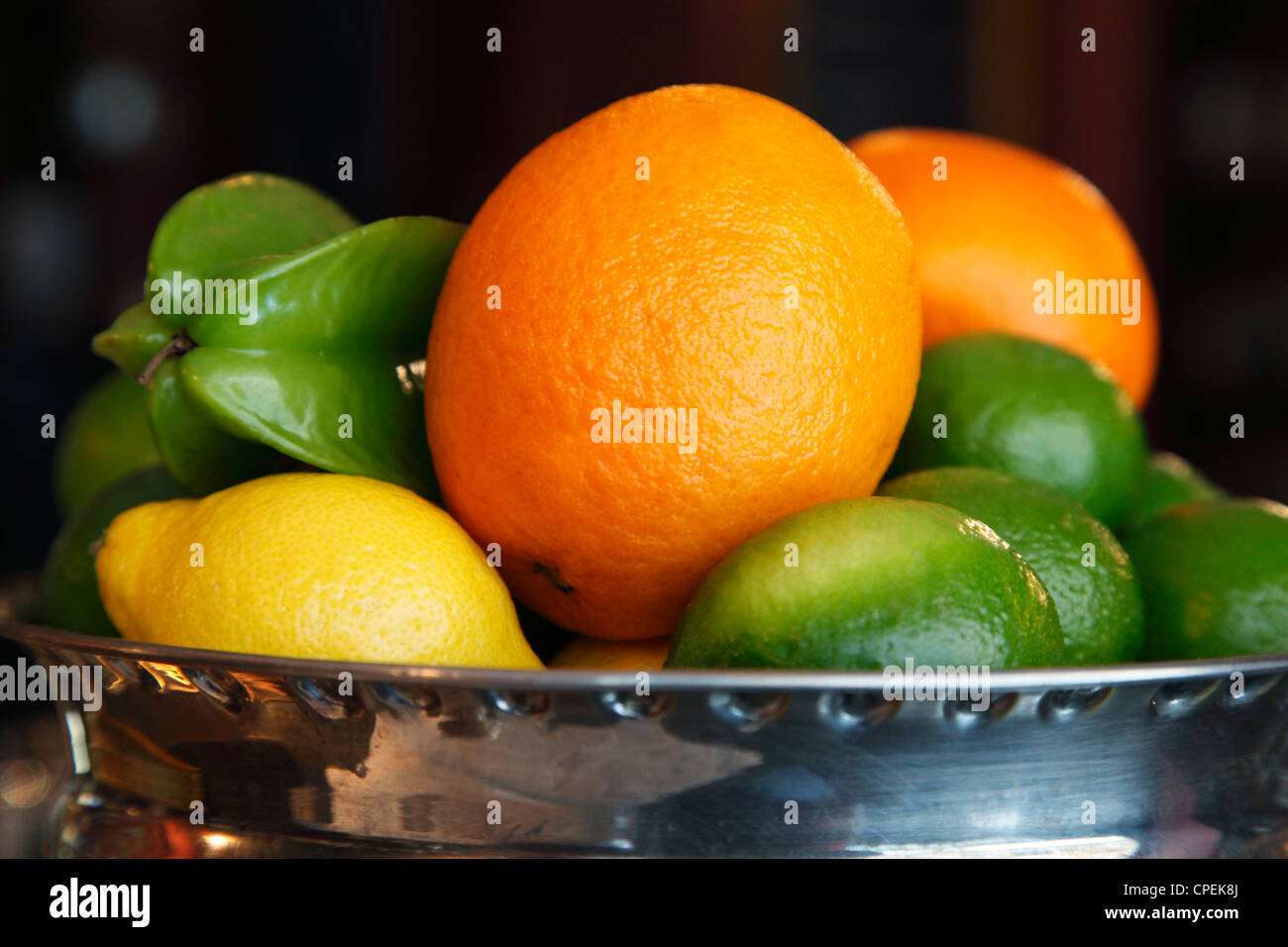 old fruit bowl with lemons oranges and star fruit - Stock Image