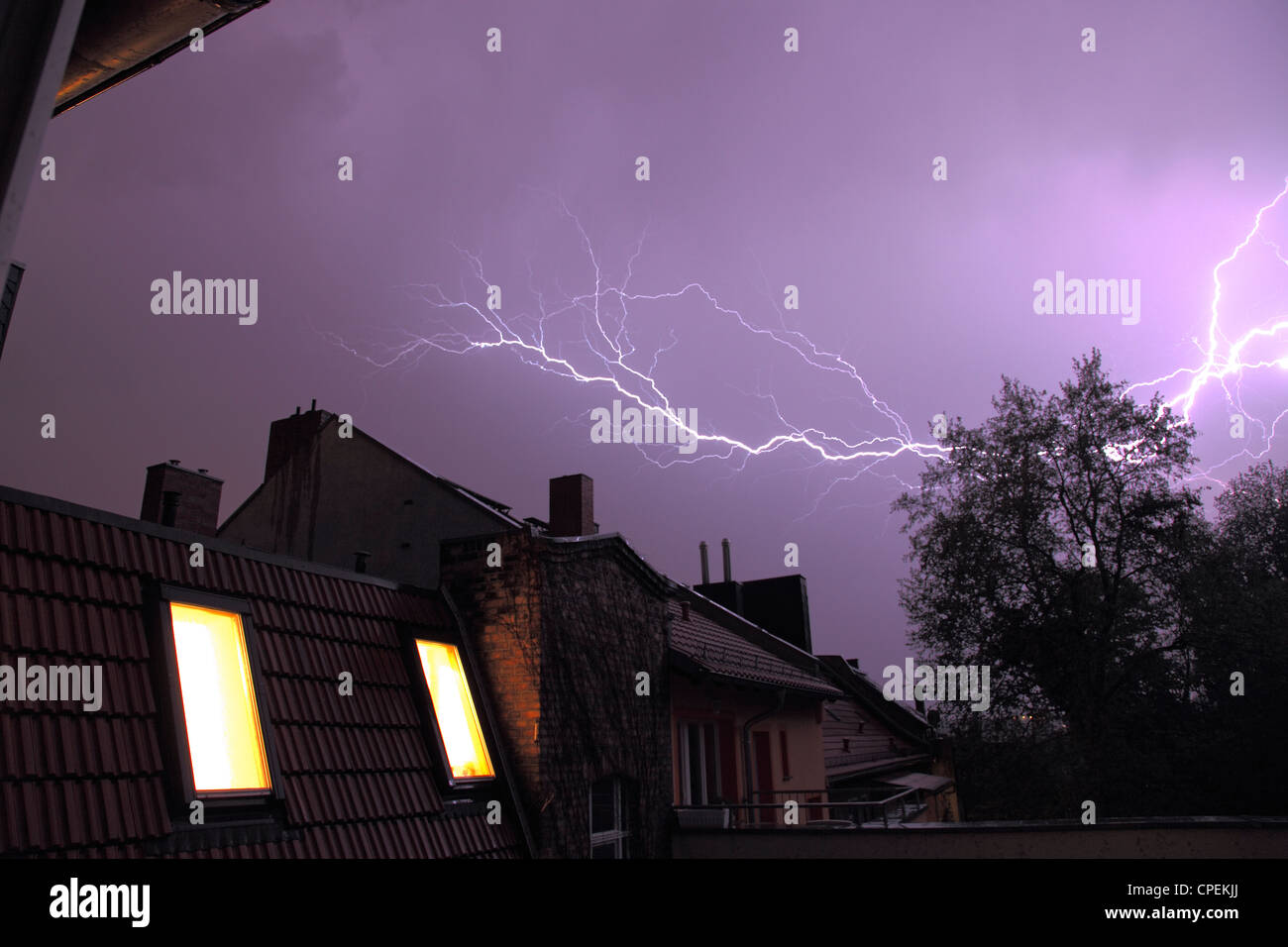 lightning storm with bolts above the rooftops of row houses - Stock Image