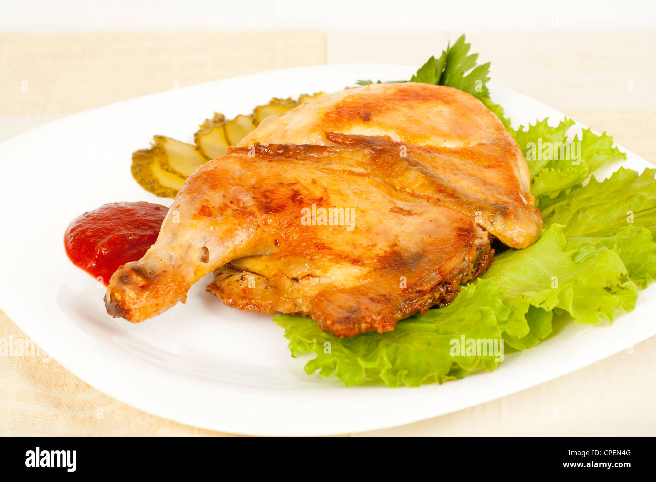 grilled chicken on a plate with pickled cucumber and tomato sauce - Stock Image