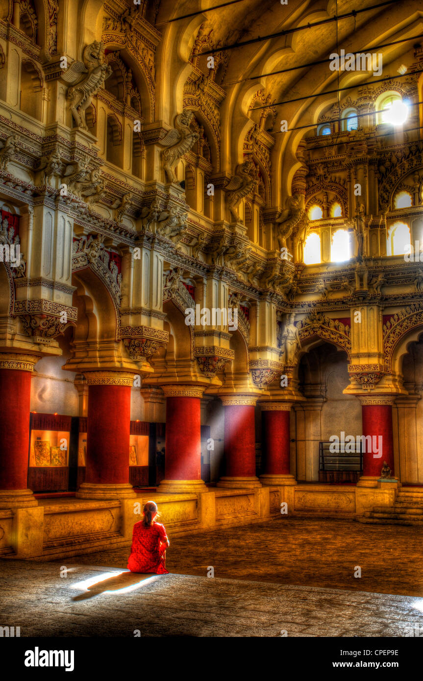 A woman in Indian dress sitting in a sunbeam in the Thirumalai Palace at Madurai, South India - Stock Image