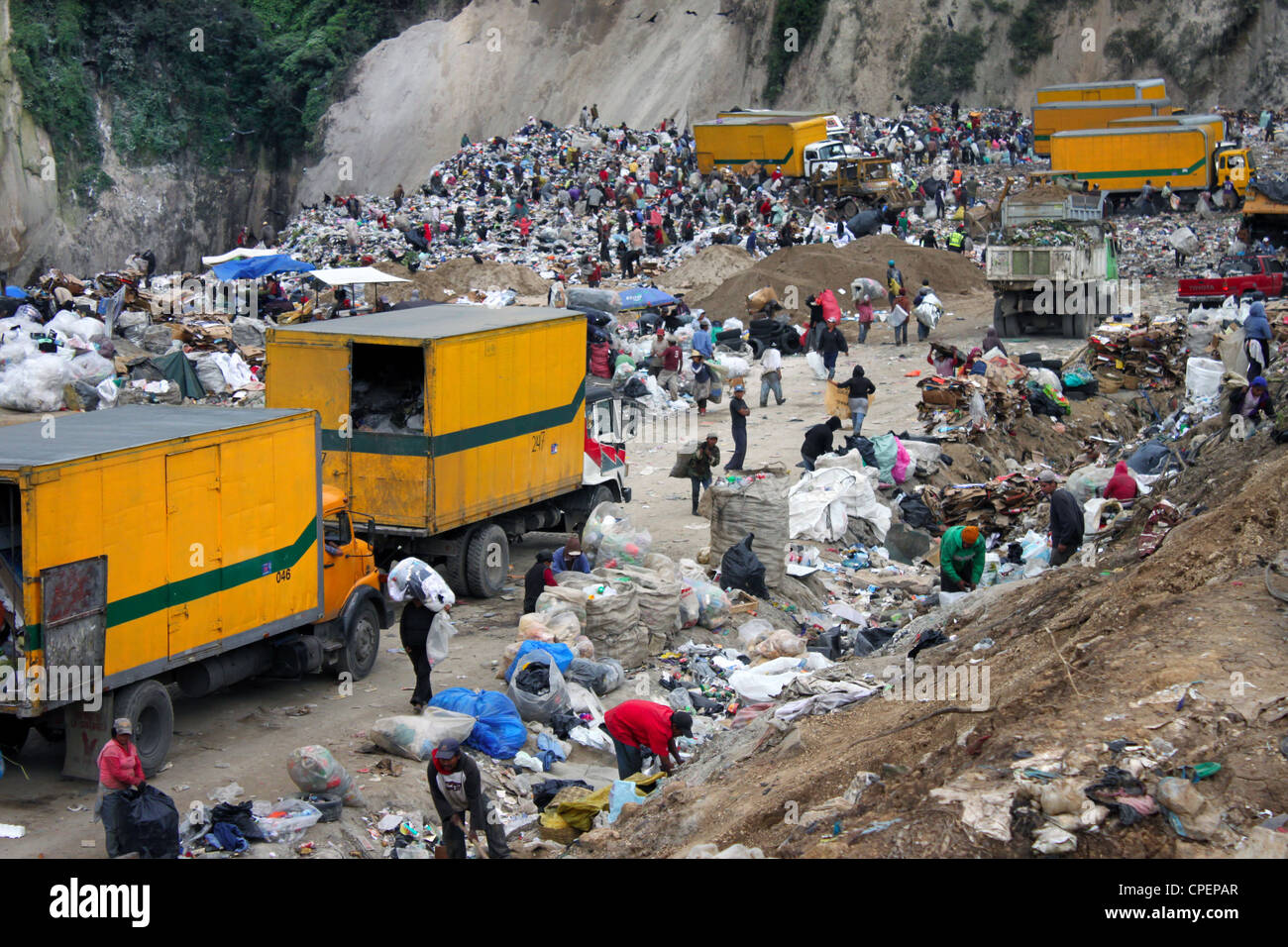 Landfill in Guatemala City. Activity of unloading garbage trucks and scavenging in a dump. - Stock Image
