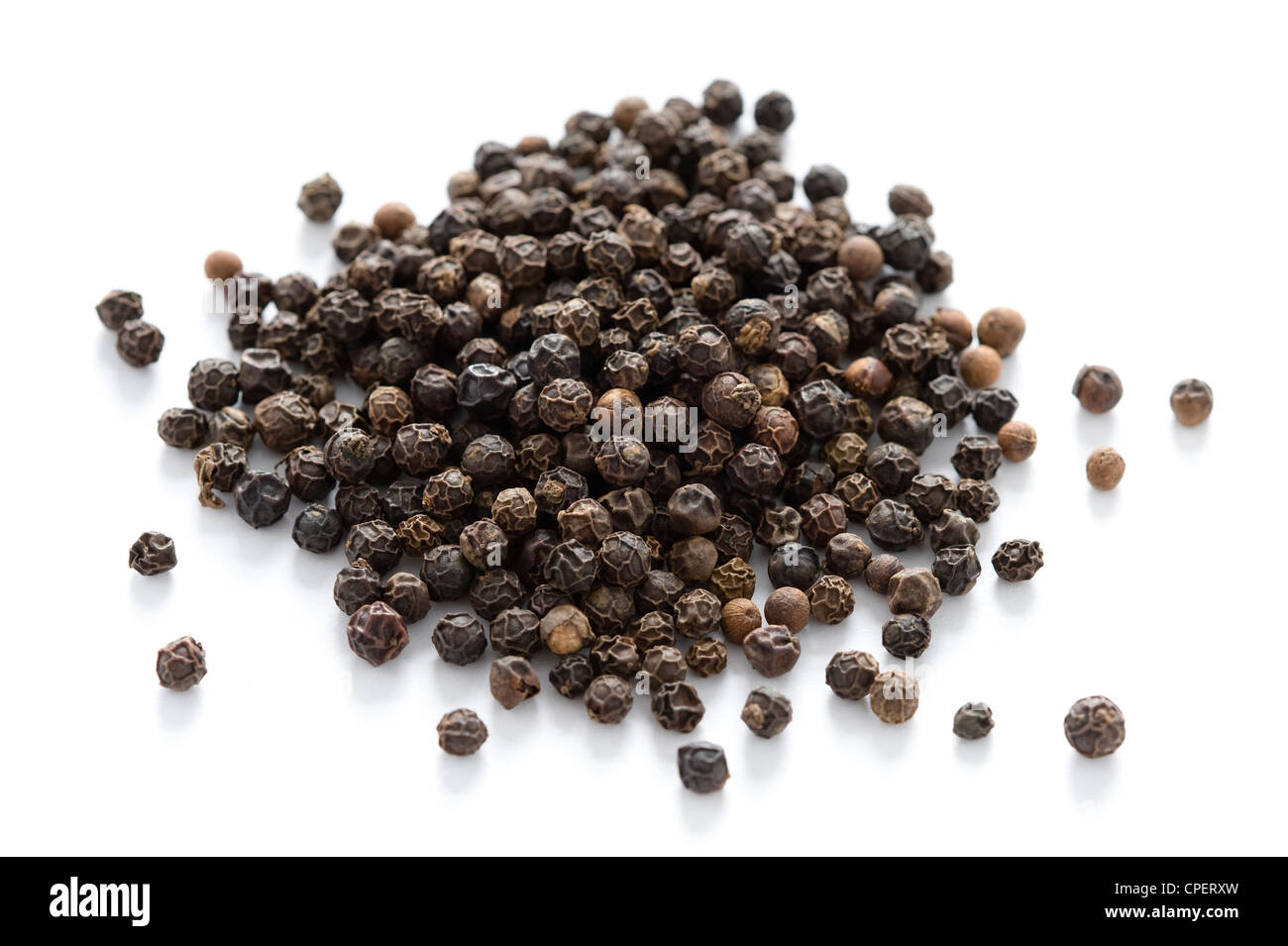 heap of black peppercorns isolated on a white background - Stock Image