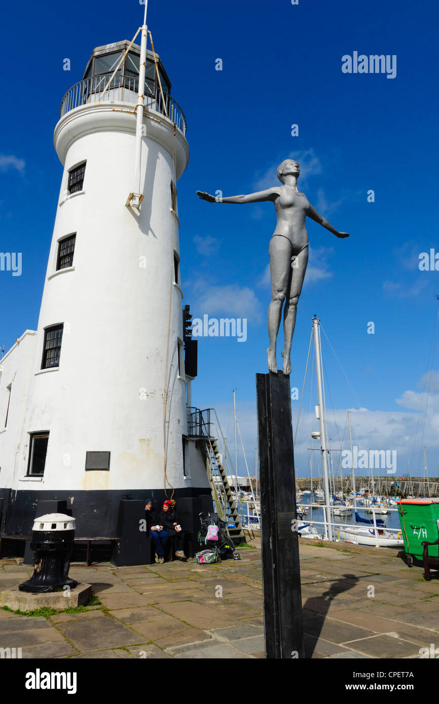 Scarborough, Yorkshire, UK - the Diving Belle sculpture next to the harbour lighthouse. - Stock Image