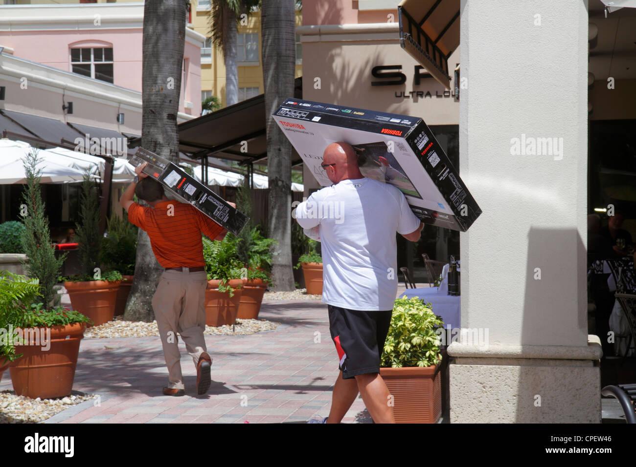 Boca Raton Florida Mizner Park Plaza Real upscale shopping business man carrying box Toshiba flat panel widescreen - Stock Image