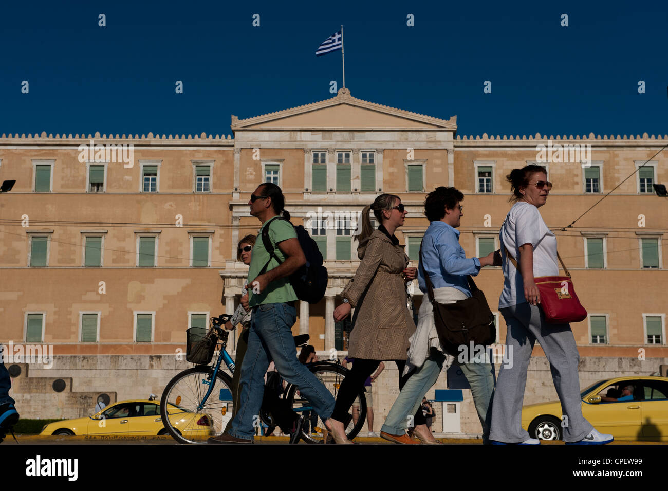 Athenians walking in front of the Greek parliament, Syntagma Sq, Athens, Greece - Stock Image