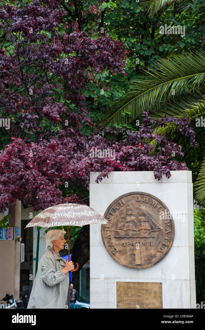 A Greek woman walking  by a plaque portraying an old drachma coin that was replaced by the euro in 2002 outside - Stock Image