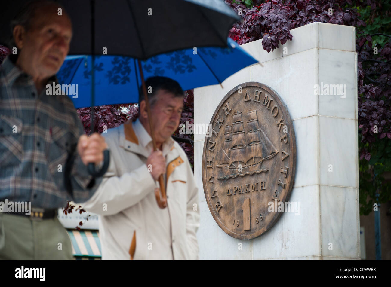 Two Greek man walking  by a plaque portraying an old drachma coin that was replaced by the euro in 2002 outside Stock Photo