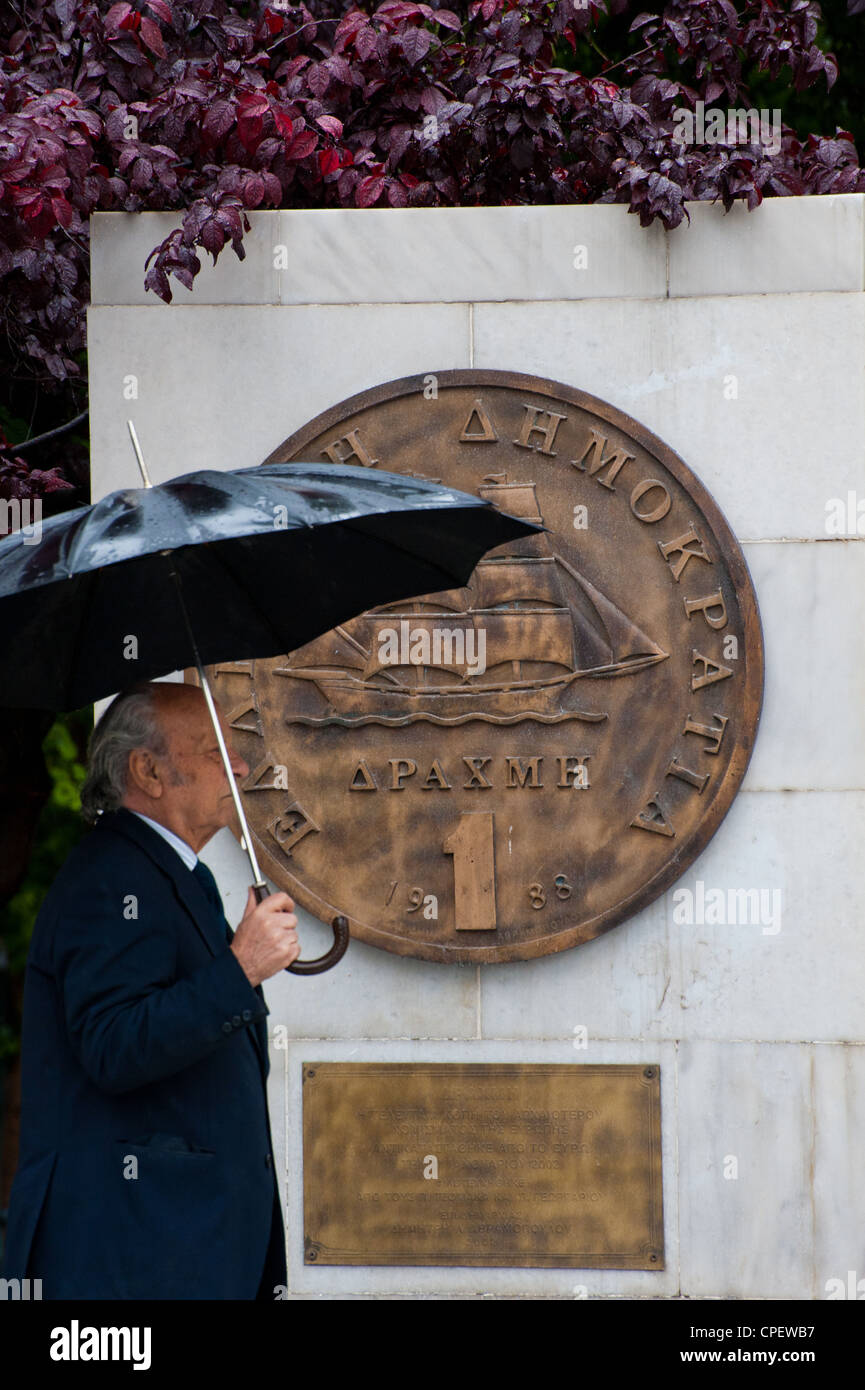 A Greek man walking  by a plaque portraying an old drachma coin that was replaced by the euro in 2002 outside Athens - Stock Image
