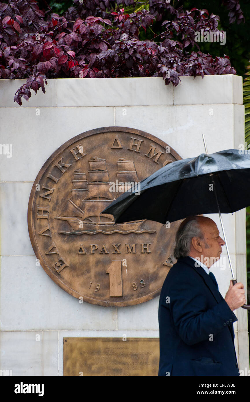 A Greek man walking  by a plaque portraying an old drachma coin that was replaced by the euro in 2002 outside Athens Stock Photo