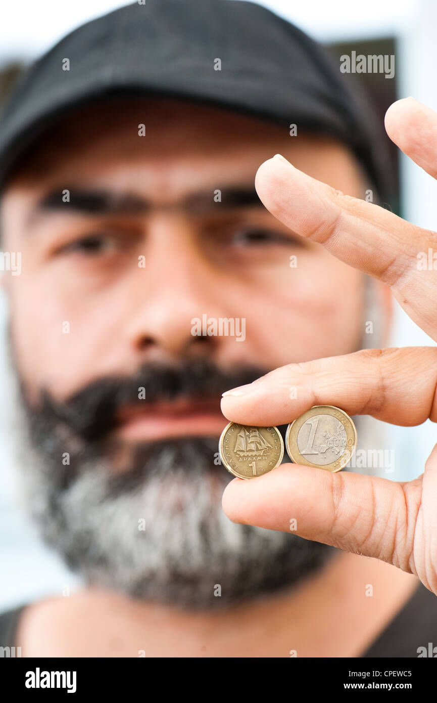 Cafe owner Nikos Bourbakis holding an old one drachma coin replaced by the euro in 2002 and a greek euro coin. - Stock Image