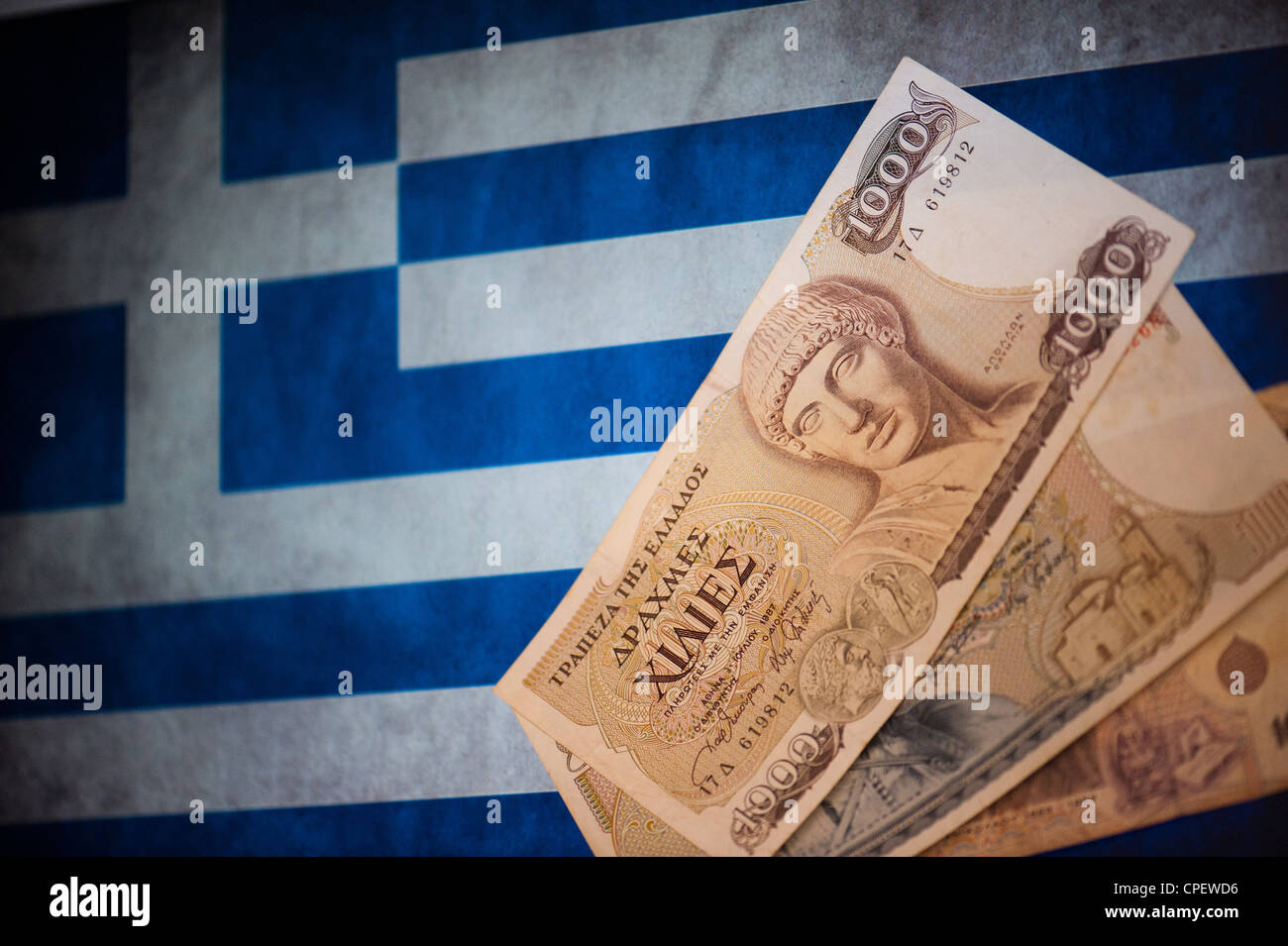 Old Greek drachma notes replaced in 2002 by the euro in front of the Greek flag - Stock Image