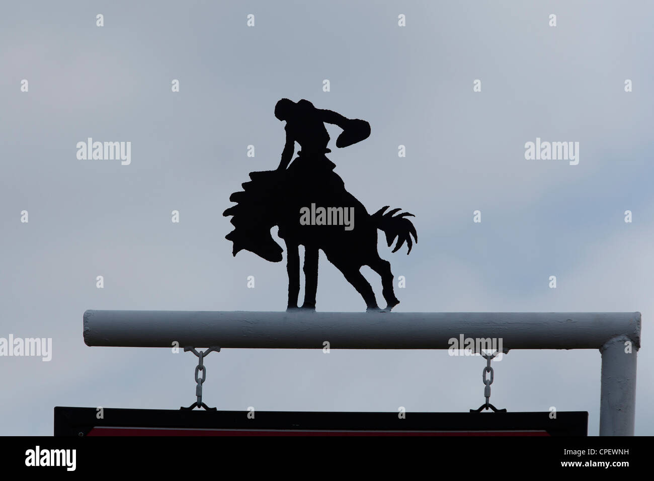 A silhouette cutout of a cowboy riding a bucking horse - Stock Image