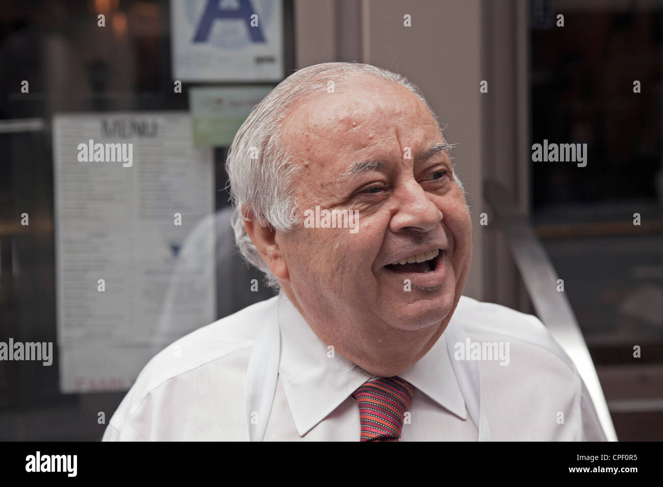 A man chats in front of the restaurant he owns in New York City. - Stock Image